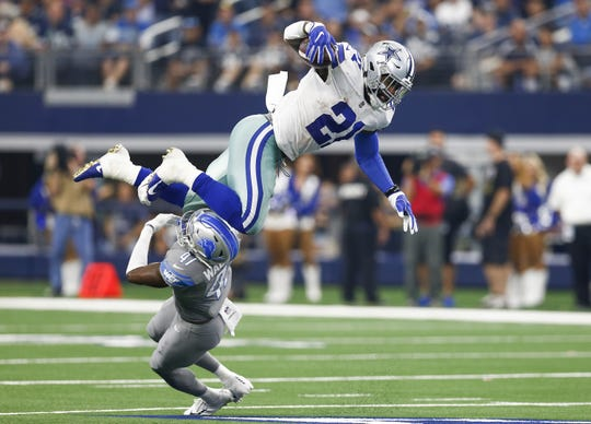 Dallas Cowboys running back Ezekiel Elliott leaps over Detroit Lions defensive back Tracy Walker on Sept. 30, 2018 at AT&T Stadium in Arlington, Texas. The Cowboys won 26-24.