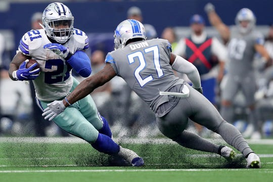Dallas Cowboys running back Ezekiel Elliott carries the ball against Detroit Lions safety Glover Quin in the fourth quarter at AT&T Stadium on Sept. 30, 2018 in Arlington, Texas.