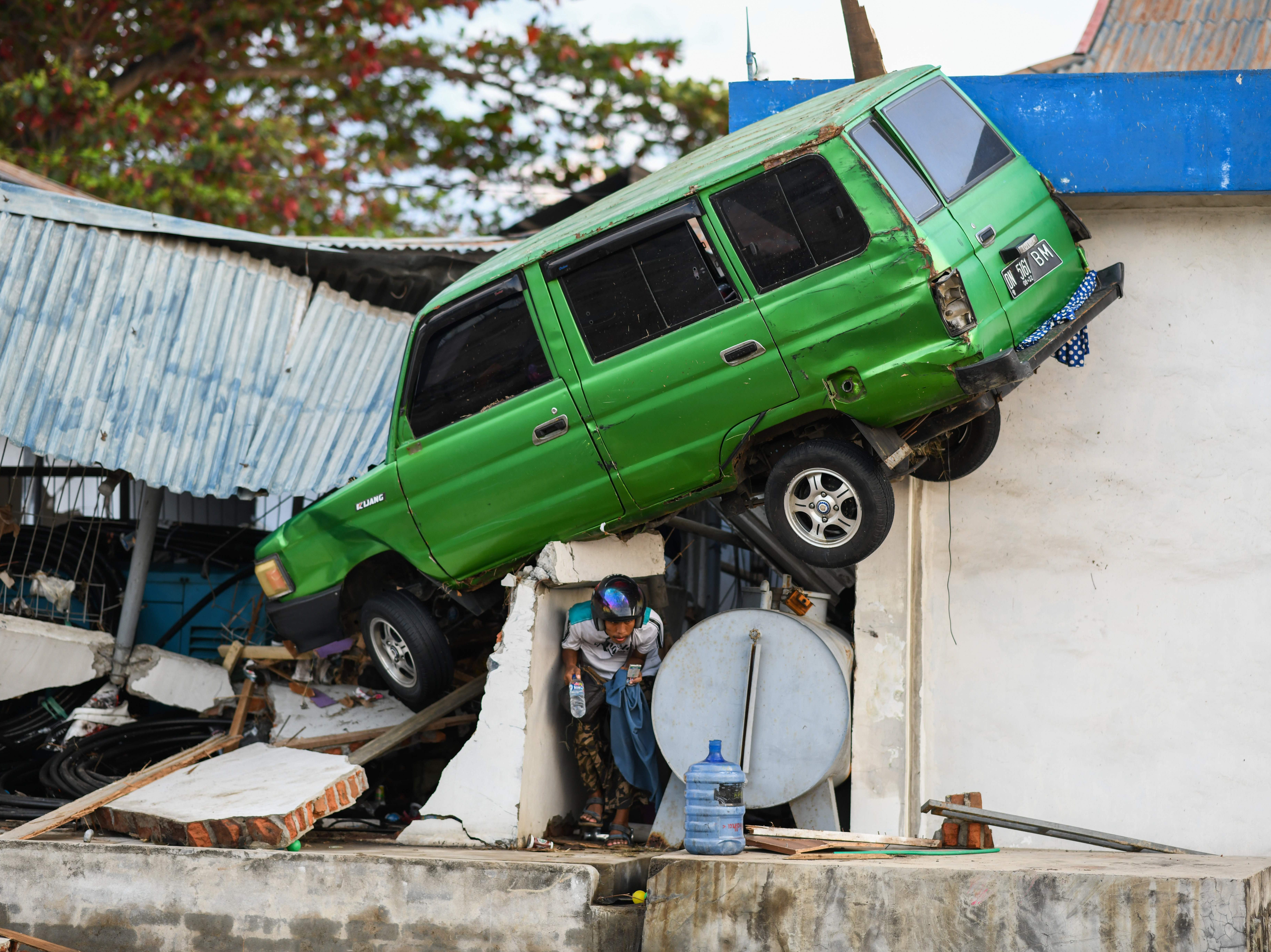 A survivor squeezes under a car stuck on a building in Palu, Indonesia's Central Sulawesi on Oct. 1, 2018. Volunteers began burying victims of a Sept. 28 quake-tsunami that devastated swathes of Sulawesi and left authorities struggling to deal with the sheer scale of the disaster.