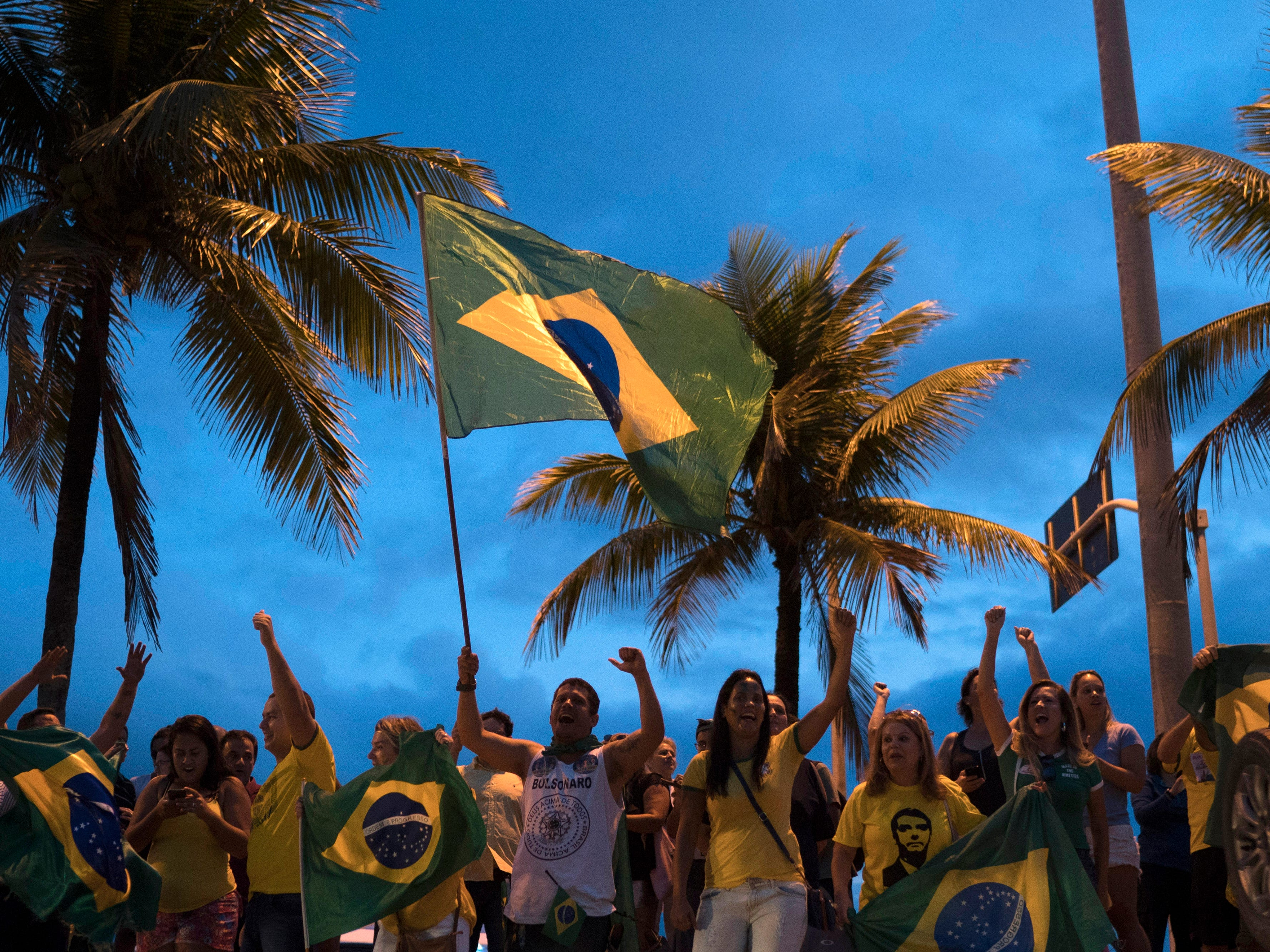 People gather in front of the condominium where leading presidential candidate Jair Bolsonaro resides to show their support, in Rio de Janeiro, Brazil, Saturday, Sept. 29, 2018. Bolsonaro, who suffered intestinal damage and severe internal bleeding after the Sept. 6 attack at a campaign event and has undergone multiple surgeries, was discharged Saturday from a Sao Paulo hospital where he was being treated.
