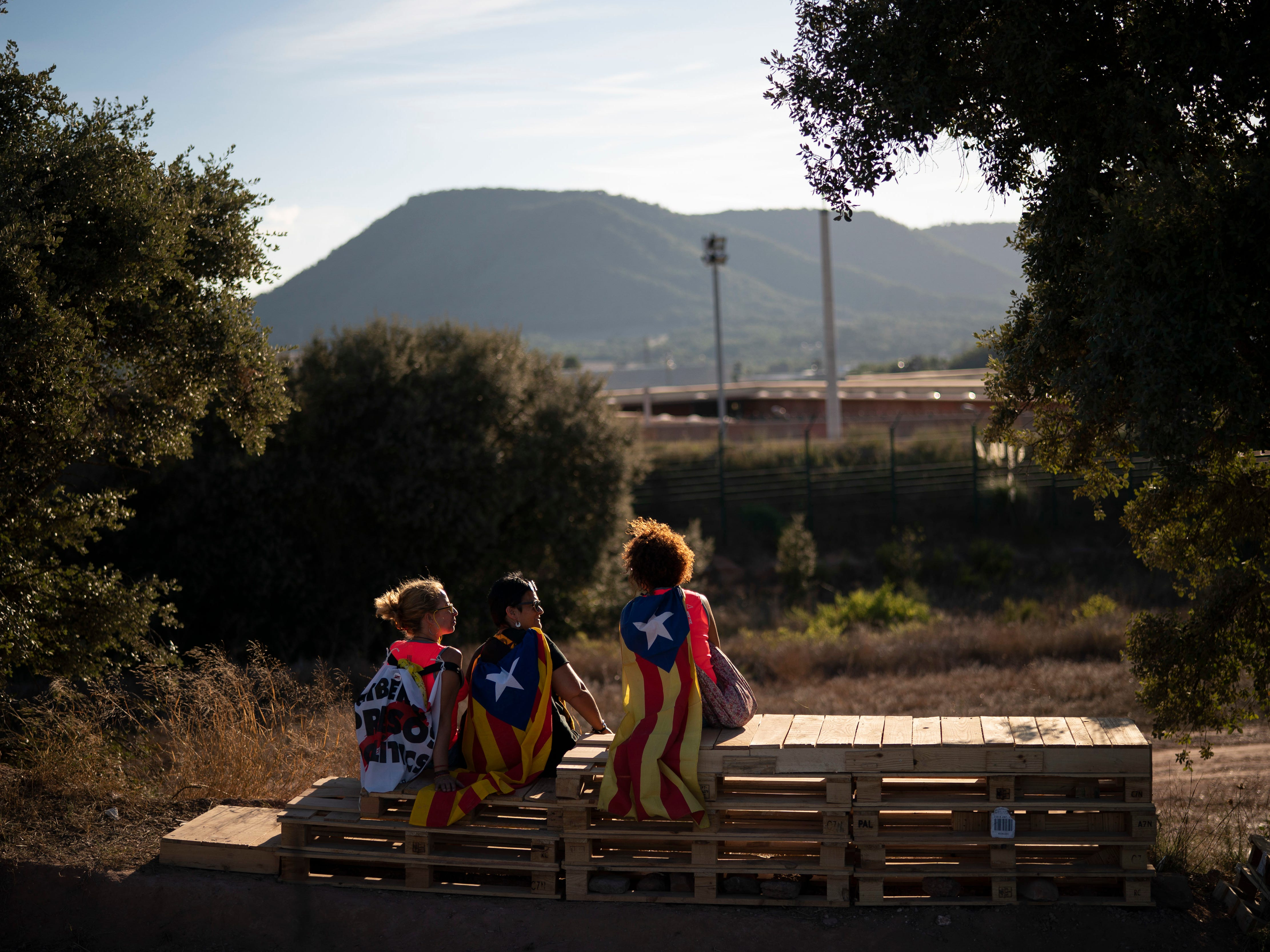 """Pro independence demonstrators, some wearing """"esteladas"""" or independence flags, sit in a field overlooking the Lledoners prison in Sant Joan de Vilatorrada, about 30 miles from Barcelona, Spain, Sunday, Sept. 30, 2018. Hundreds of Catalonia residents gathered near the Lledoners prison, where most prominent jailed separatists are awaiting trial, to mark nearly one-year since an unauthorized independence referendum was held in this region of Spain last year."""