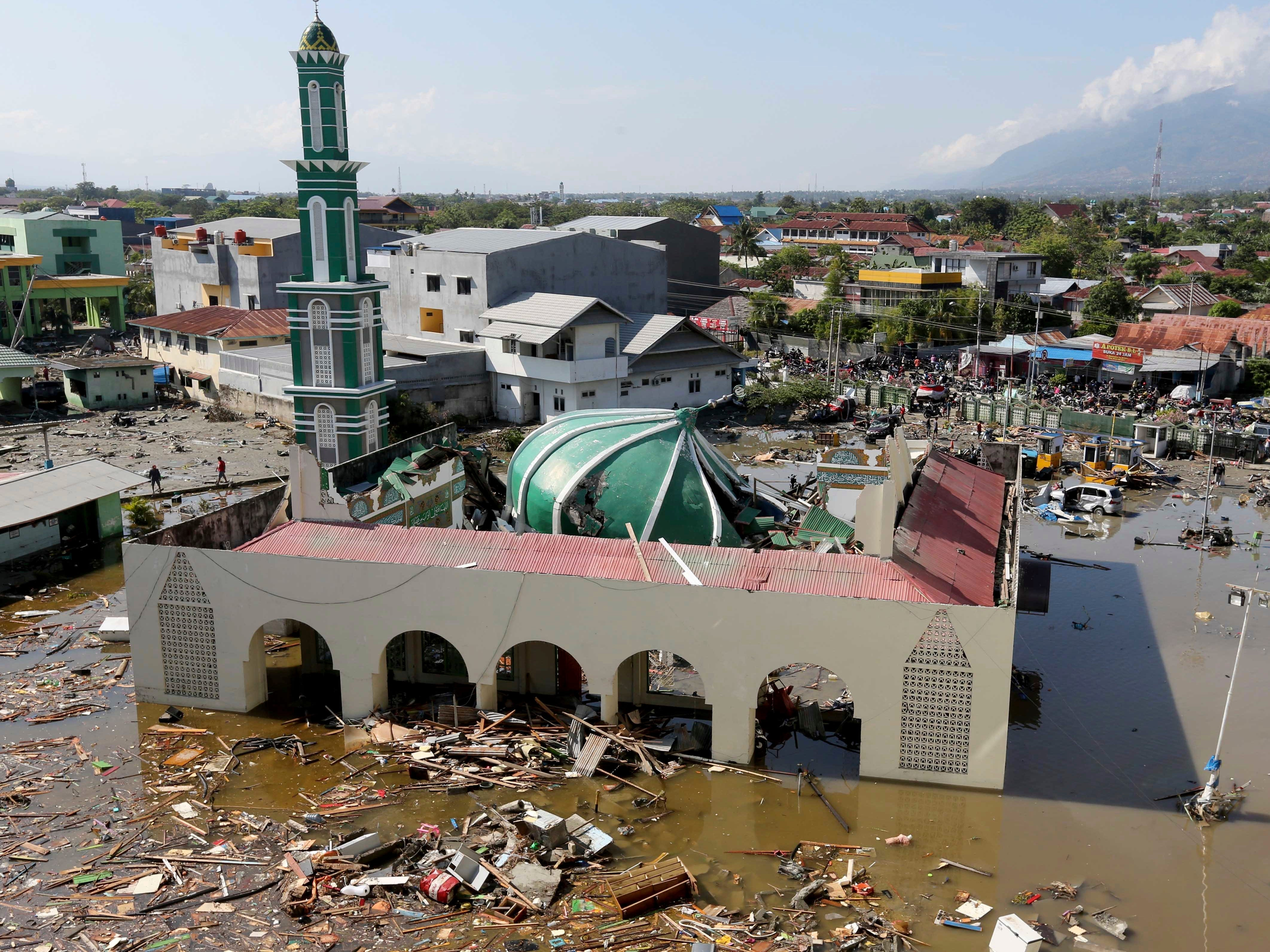 People survey the mosque damaged following earthquakes and tsunami in Palu, Central Sulawesi, Indonesia, Sunday, Sept. 30, 2018. A tsunami swept away buildings and killed hundreds on the Indonesian island of Sulawesi.