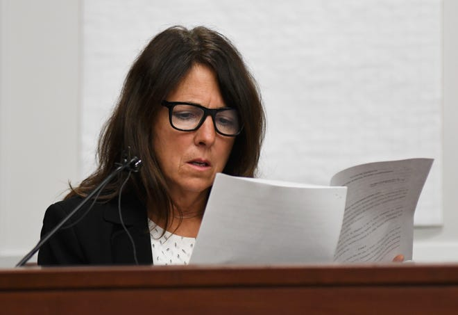 Livingston County Judge Theresa Brennan reads a transcript as she gives testimony during her judicial misconduct proceeding in the courtroom of Judge William Giovan, Monday in Livonia.