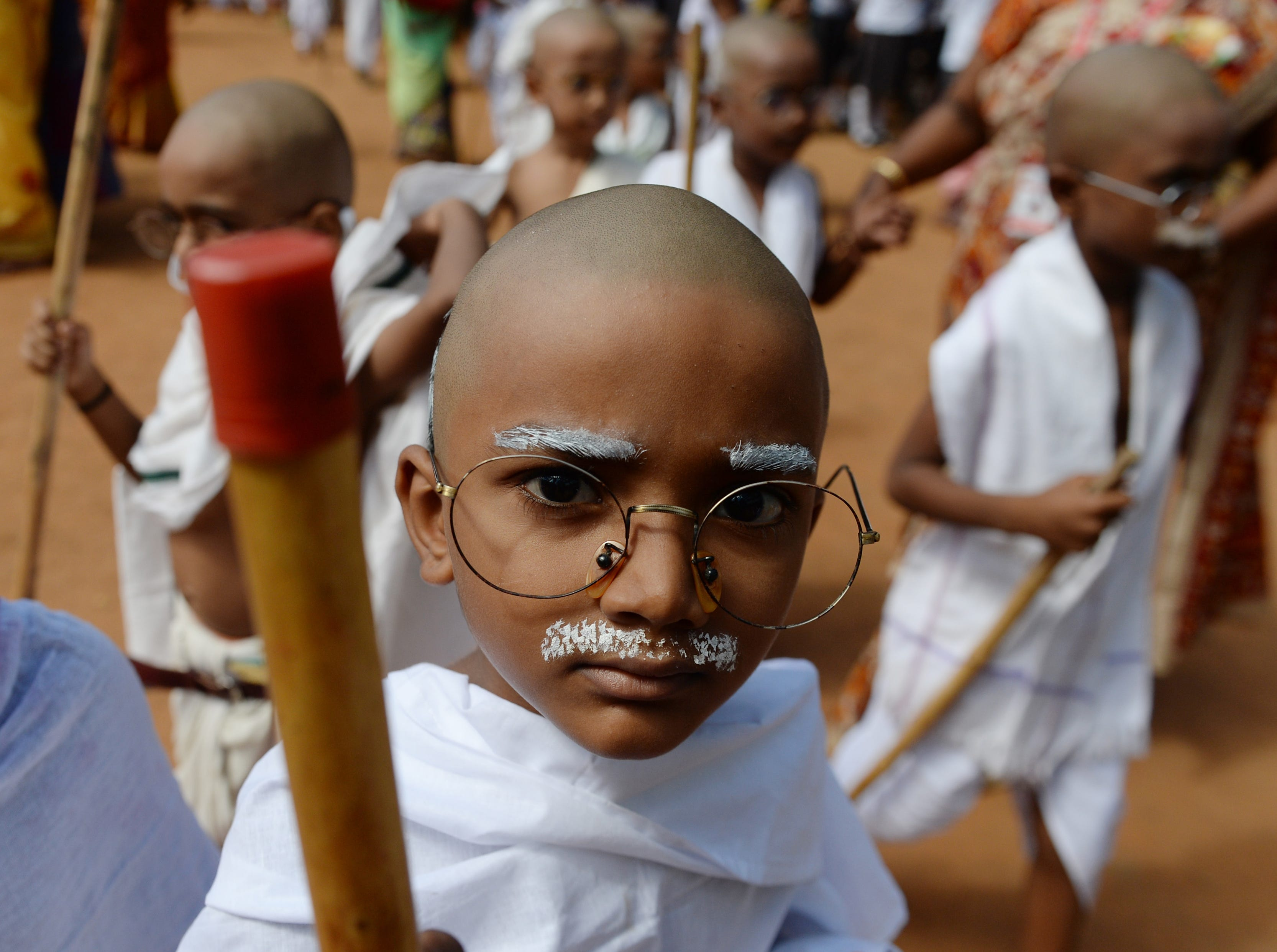 Indian children with their heads shaved and dressed like Mahatma Gandhi assemble during a school event in Chennai on Oct. 1, 2018, the day before Gandhi's birth anniversary.