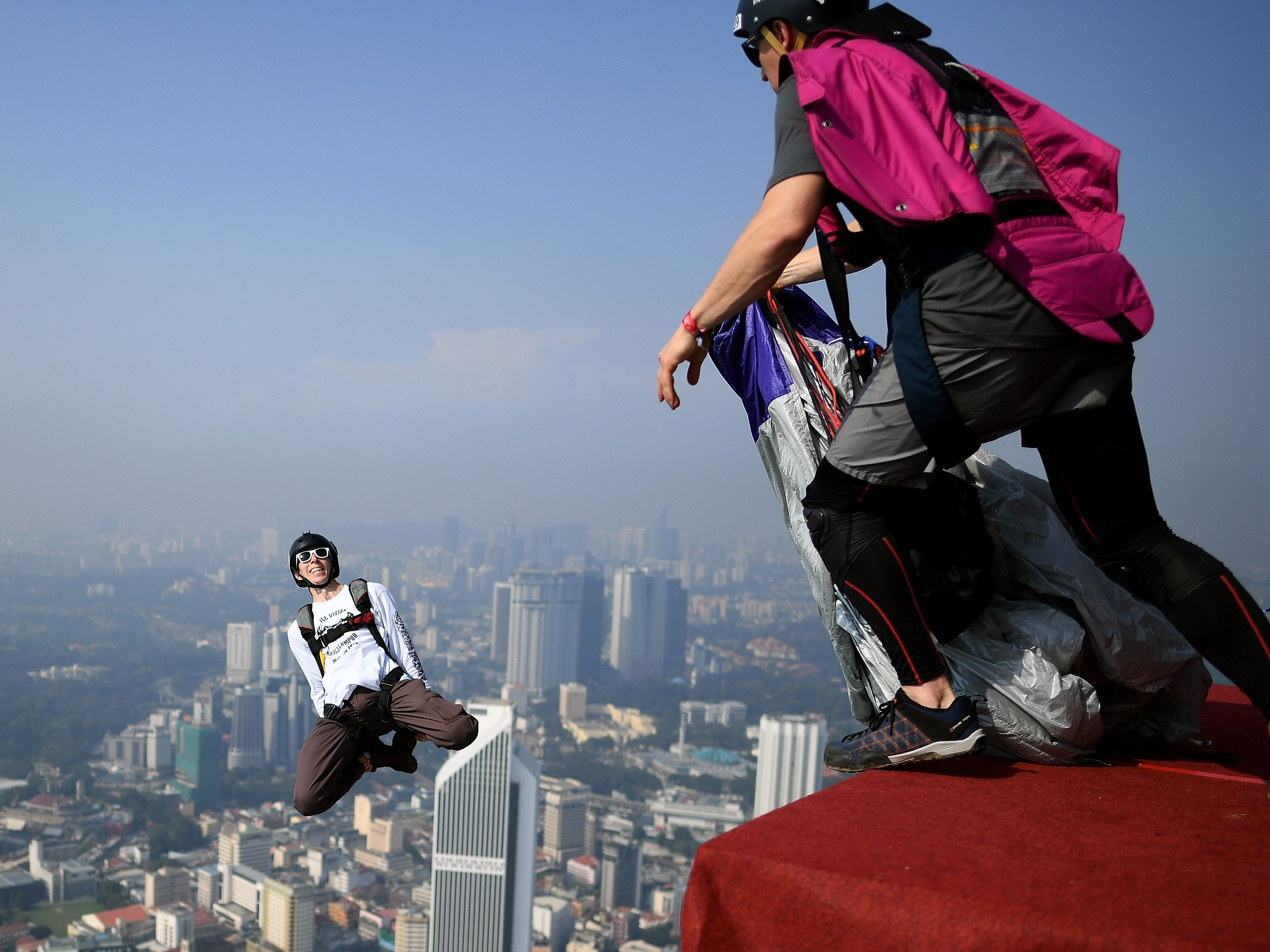 Base jumpers leap from the 300-metre high skydeck of Malaysia's landmark Kuala Lumpur Tower against the backdrop of the city's skyline in Kuala Lumpur on Sunday, Sept. 30, 2018 during the annual International KL Tower Base-Jump event.