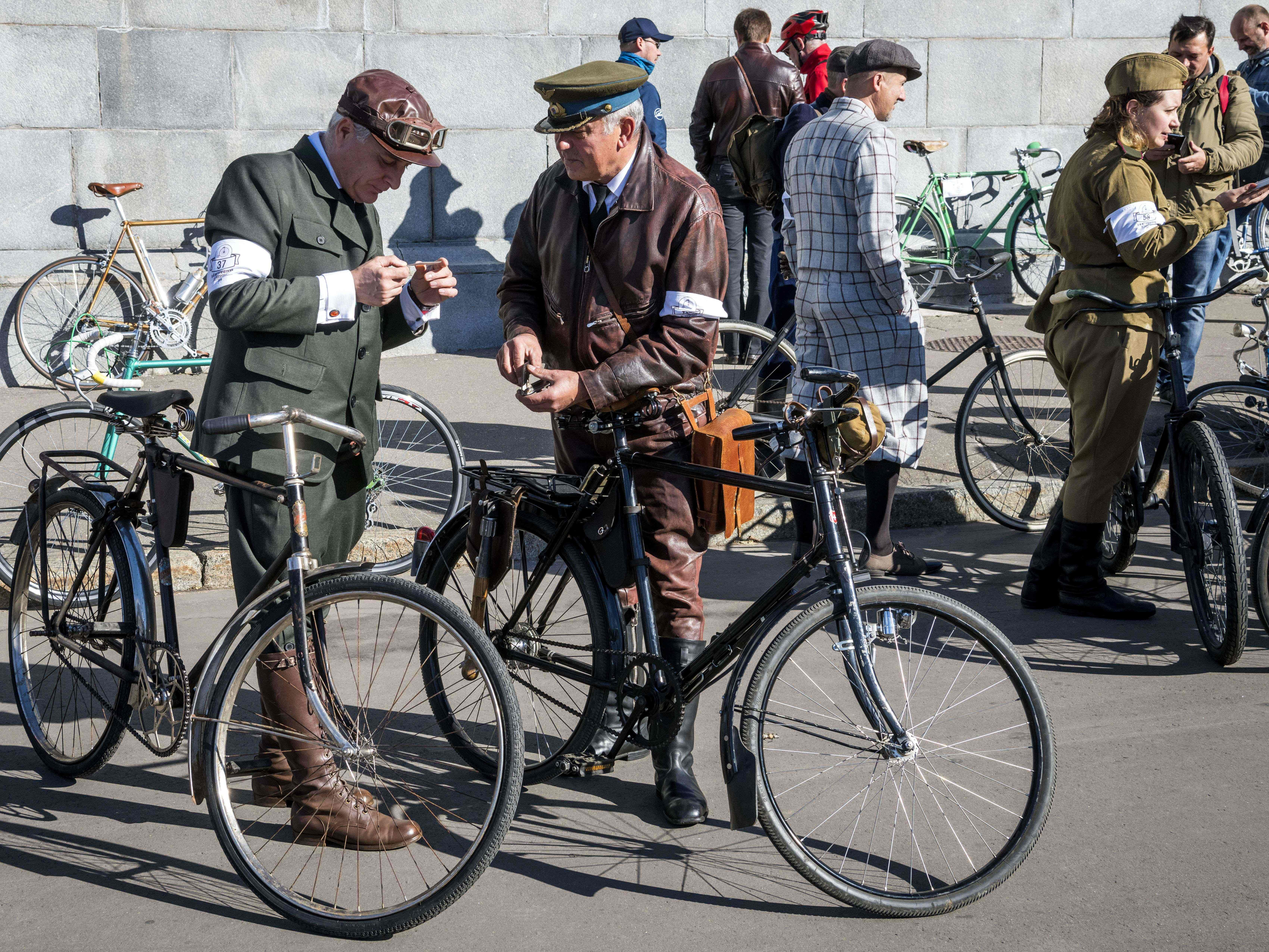 Bicycle enthusiasts dressed in vintage clothing gather at Gorky Park entrance for the annual retro bicycle parade in Moscow on Sept. 30, 2018.
