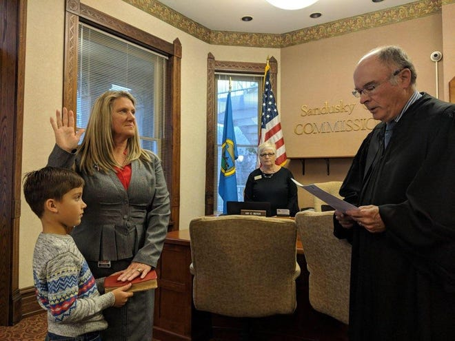 Kim Foreman, with grandson Walter Foreman at her side, is sworn in by Sandusky County Common Pleas Court Judge John Dewey Monday as new county treasurer.