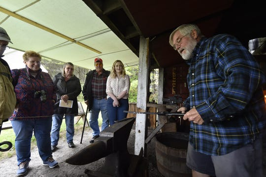 Blacksmith Rolf Olson demonstrates iron forging to Door County Executive Director Bailey Koepsel, right, and visitors John and Bonnie Wetter of Beloit, and Pat and Tom Kitsembel of Jefferson at Heritage Village at Big Creek on Friday.