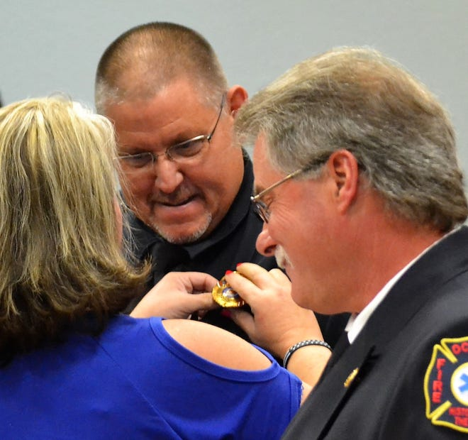 Ann Rehberg pins the police chief's badge on the uniform of her husband Mike at a ceremony Friday, Sept. 28 at Oconto City Hall. At right is Fire Chief John Reed.