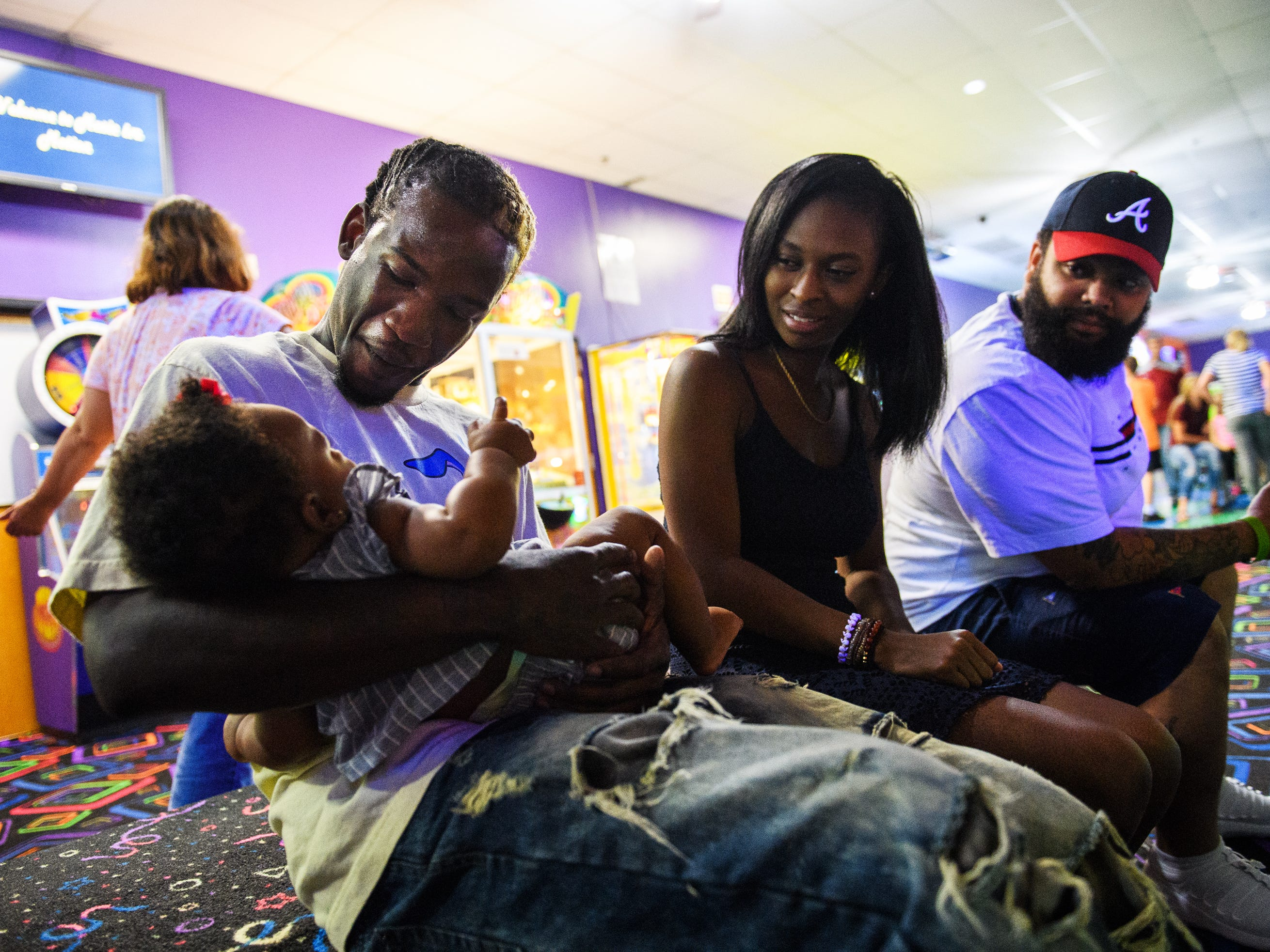 Isiah Kinloch holds Oakland Rae Patrick as he hangs out with Jordyn Patrick and Dominique Mccants at Music In Motion Family Fun Center in Summerville for his son's birthday party on July 29, 2018.