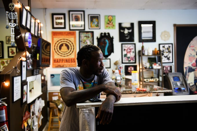 Isiah Kinloch waits for customers to arrive at Artistic Ink in Summerville, where he works as a tattoo artist, Friday, July 27, 2018. Kinloch had a run-in with North Charleston Police in 2015 that changed his life.