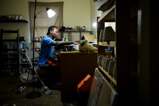 Isiah Kinloch cleans shoes in his home July 29, 2018. The tattoo artist picks up side jobs, like shoe repair and sales. He lost his rent money after calling 911 to report an intruder had attacked him.