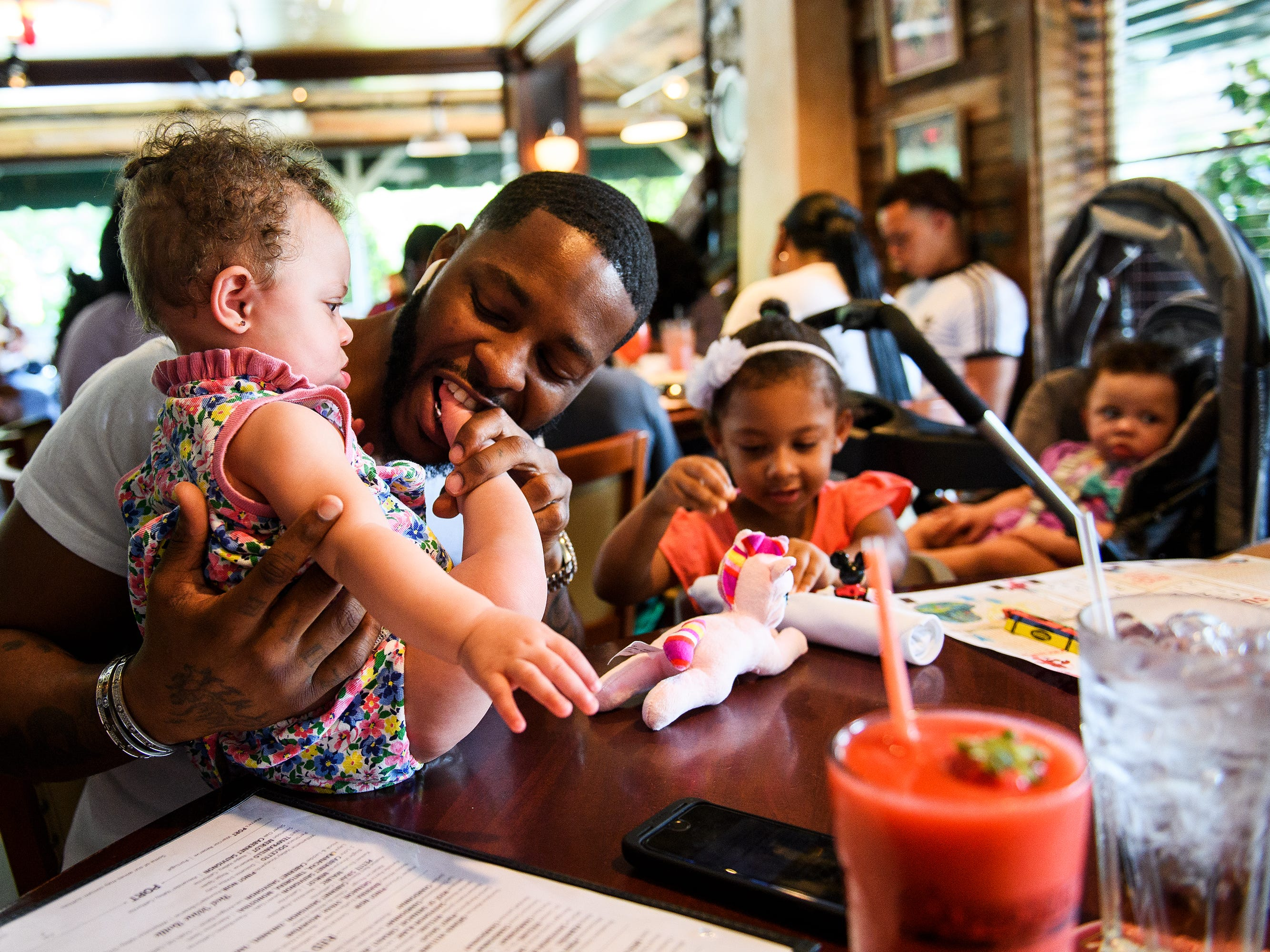 Johnnie Grant plays with his nine-month-old daughter, Rayna, while out to eat with his family in Atlanta. Grant had money taken by cops in South Carolina despite showing them receipts and other business paperwork proving the cash came from his job.