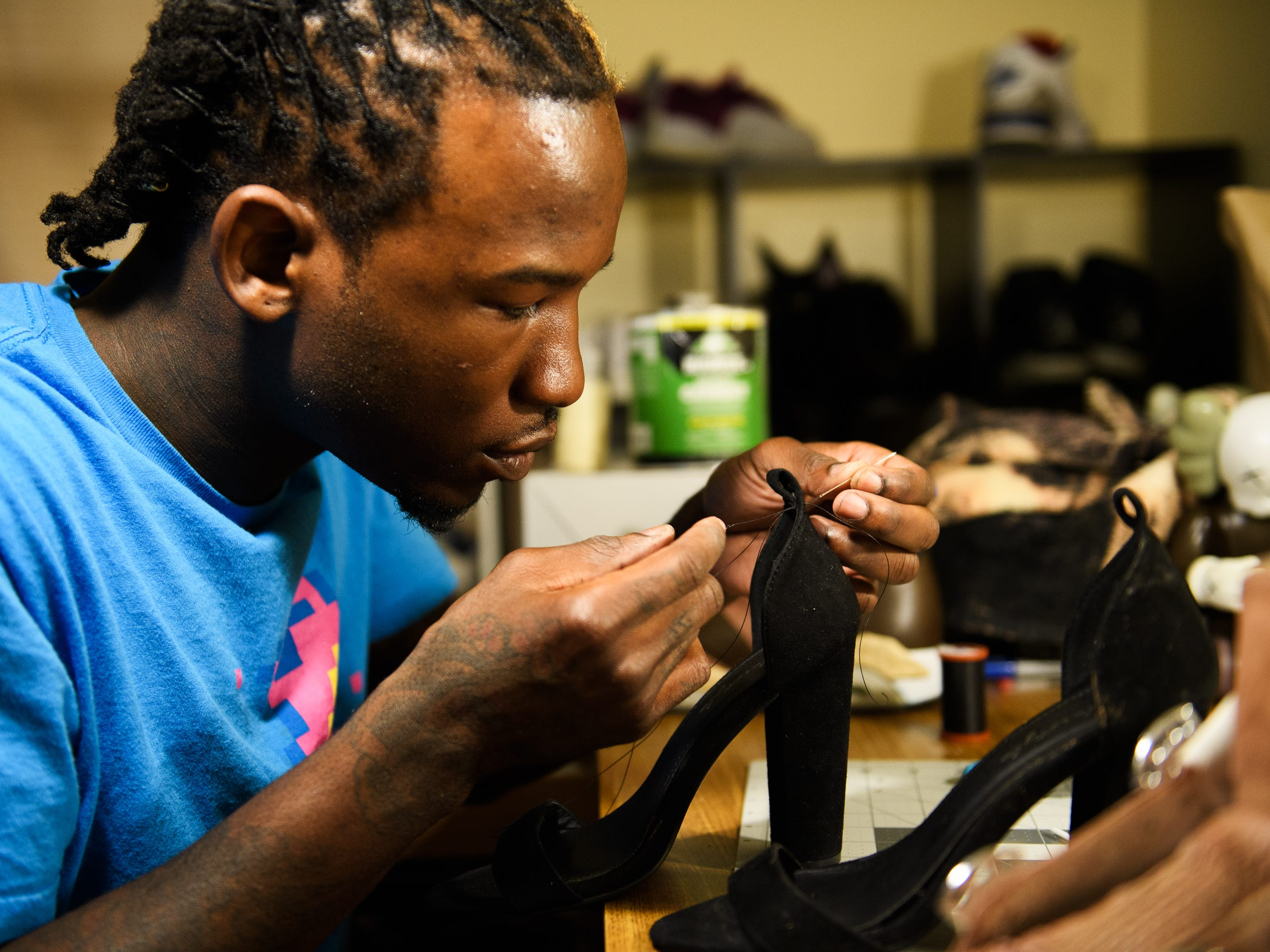 Isiah Kinloch repairs the back heel strap of a pair of shoes for a friend. During an incident that has changed his life, Kinloch fought off a robber who barged into his apartment and attacked him. The defining moment: police found and seized his money while he was at the hospital being treated for his injuries.