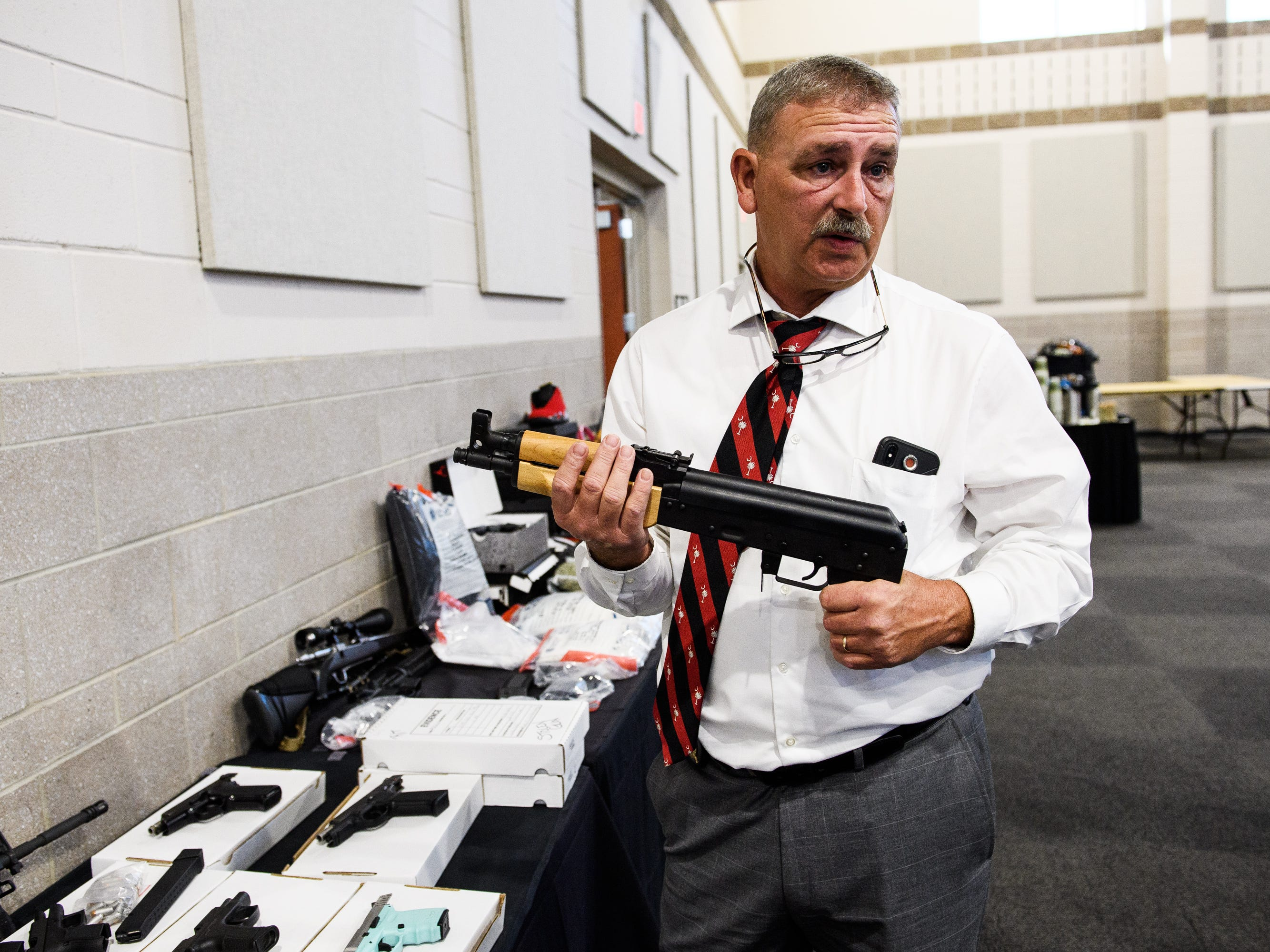 A staunch defendant of civil forfeiture, Spartanburg County Sheriff Chuck Wright holds one of the guns seized during last year's Operation Rolling Thunder on Friday, May 4, 2018.