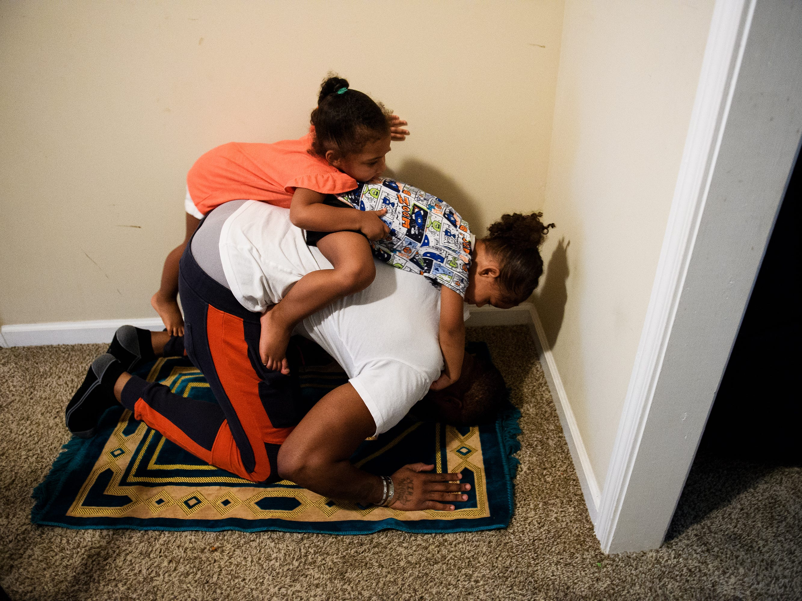 Yahya Grant and her brother Aliyah catch a ride their father's back as he prays.