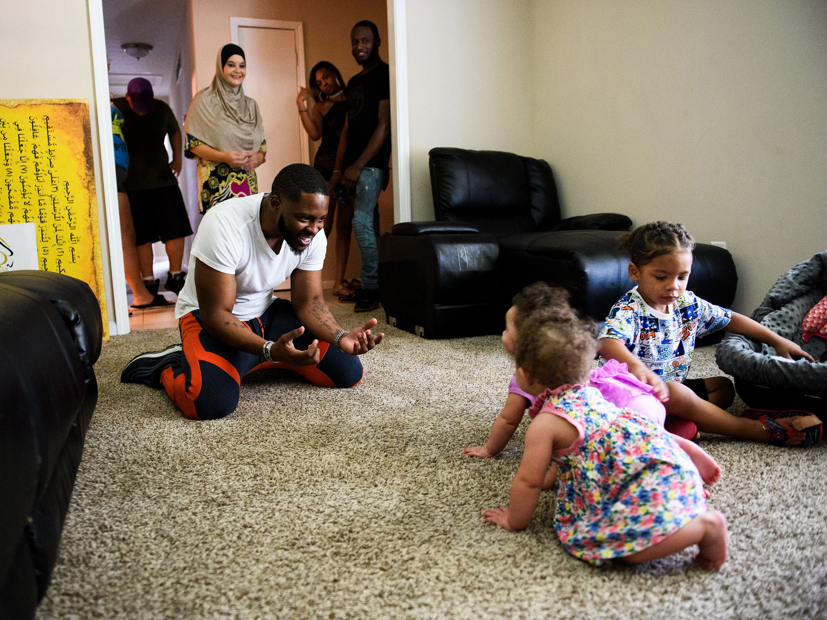 Johnnie Grant plays with his twin daughters, Alayna and Raynaon, and his son Yahya, 2.