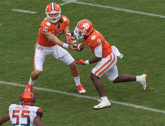 Clemson quarterback Trevor Lawrence (16) hands off to running back Travis Etienne (9) near Syracuse defensive lineman Kendall Coleman(55) during the first quarter in Memorial Stadium on Saturday, September 29, 2018.