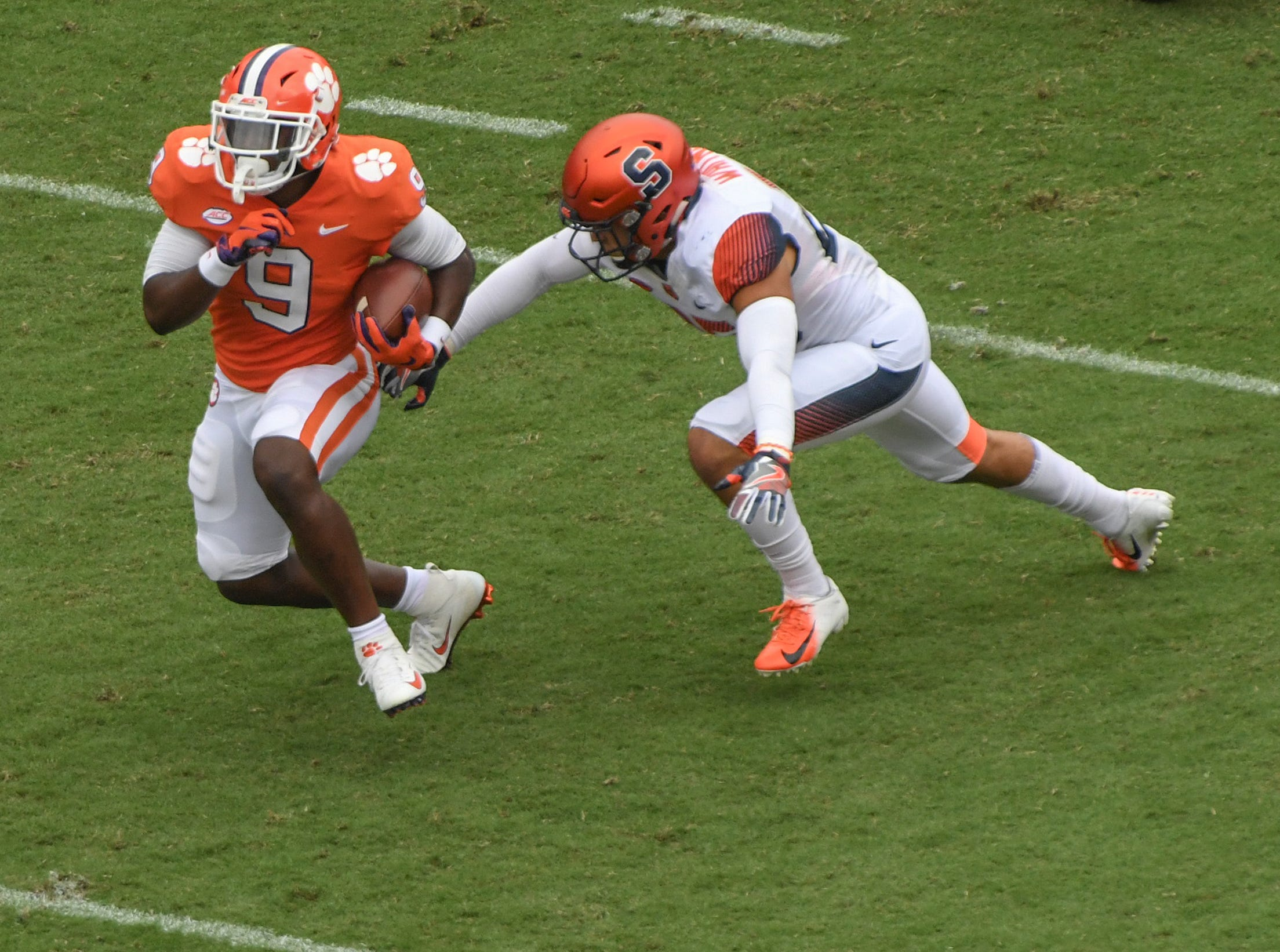 Clemson running back Travis Etienne (9) runs by a Syracuse player during the first quarter in Memorial Stadium on Saturday, September 29, 2018. Etienne credits the offensive linemen for allowing him to score three touchdowns against Syracuse.