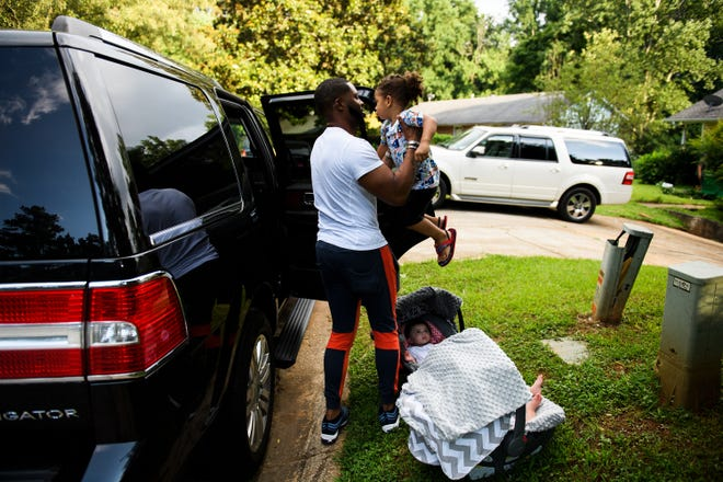 Johnnie Grant picks up his two-year-old son, Yahya, after he ran to the car to welcome him and his sisters  June 30, 2018. The musician is on the road a lot. While driving through South Carolina, he had thousands of dollars taken from him.
