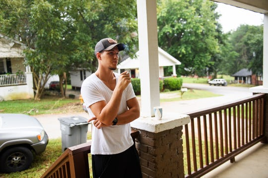 Taylor Smith smokes a cigarette on the porch of his new home, where he lives with others recovering from addiction. Smith, who was clean for more than a year while staying at Freedom House, recently relapsed from his recovery, but he says he is serious about committing to the difficult path of sobriety again.