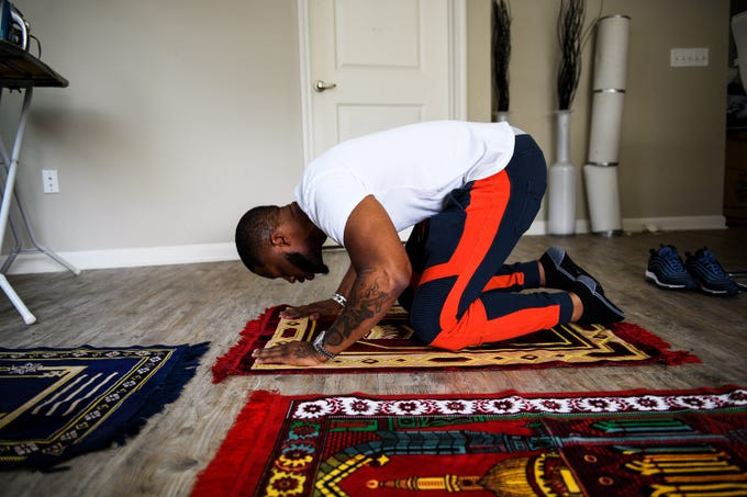Johnnie Grant, an Atlanta-based rapper, prays in his apartment before meeting his wife and children for dinner on June 30, 2018.