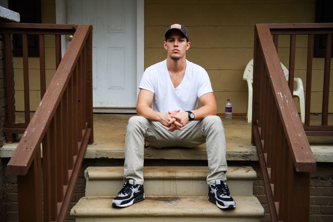 Taylor Smith, who is in recovery, sits in front of his new home. Smith has struggled with addiction for several years.