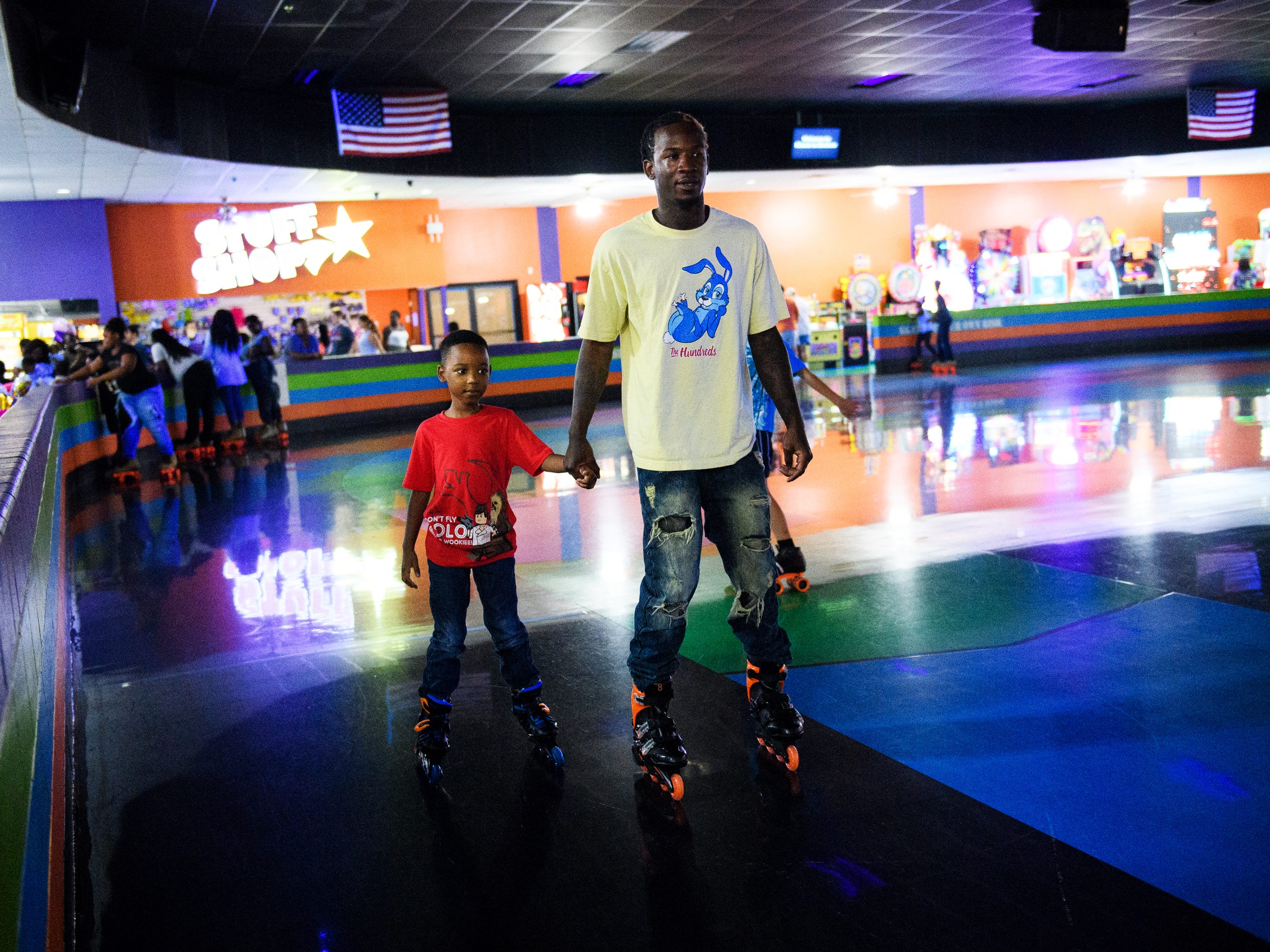 Isiah Kinloch roller blades with his son Robbie Johnson, 7, during his birthday party at Music In Motion Family Fun Center.