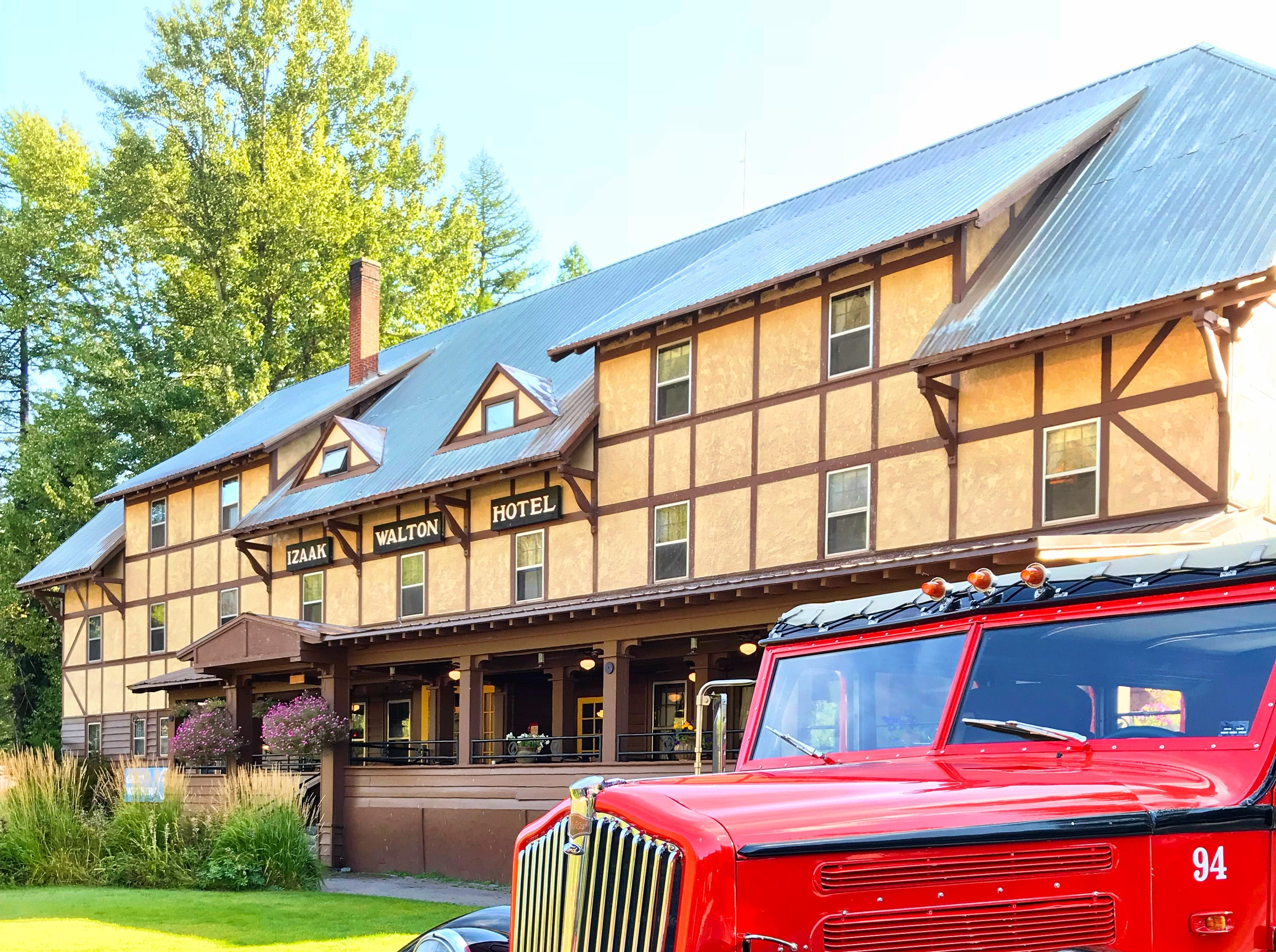 An iconic red bus is parked at the Izaak Walton Inn near Glacier National Park