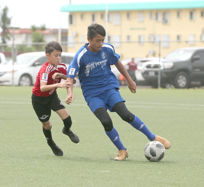 Guam Shipyard Wolverines' Hoben Barcinas maneuvers the ball around Wings FC's Gavin Baker in a Week 3 match of the Aloha Maid Minetgot Cup Elite Youth League U13 Division Saturday at the Guam Football Association National Training Center. The Wolverines and Wings settled for a 3-3 draw.