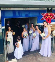 Sarah Johnson and her wedding party in the dugout of Victory Field.