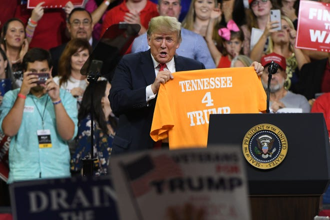 President Donald Trump holds up a Tennessee for Trump shirt during the Make America Great Again Rally for Marsha Blackburn at Freedom Hall on Monday, October 1, 2018 in Johnson City.