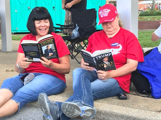 Annette Krc and Lisa Pugh read to pass the time while waiting to see President Donald Trump at Freedom Hall Civic Center in Johnson City on Monday, Oct. 1, 2018.