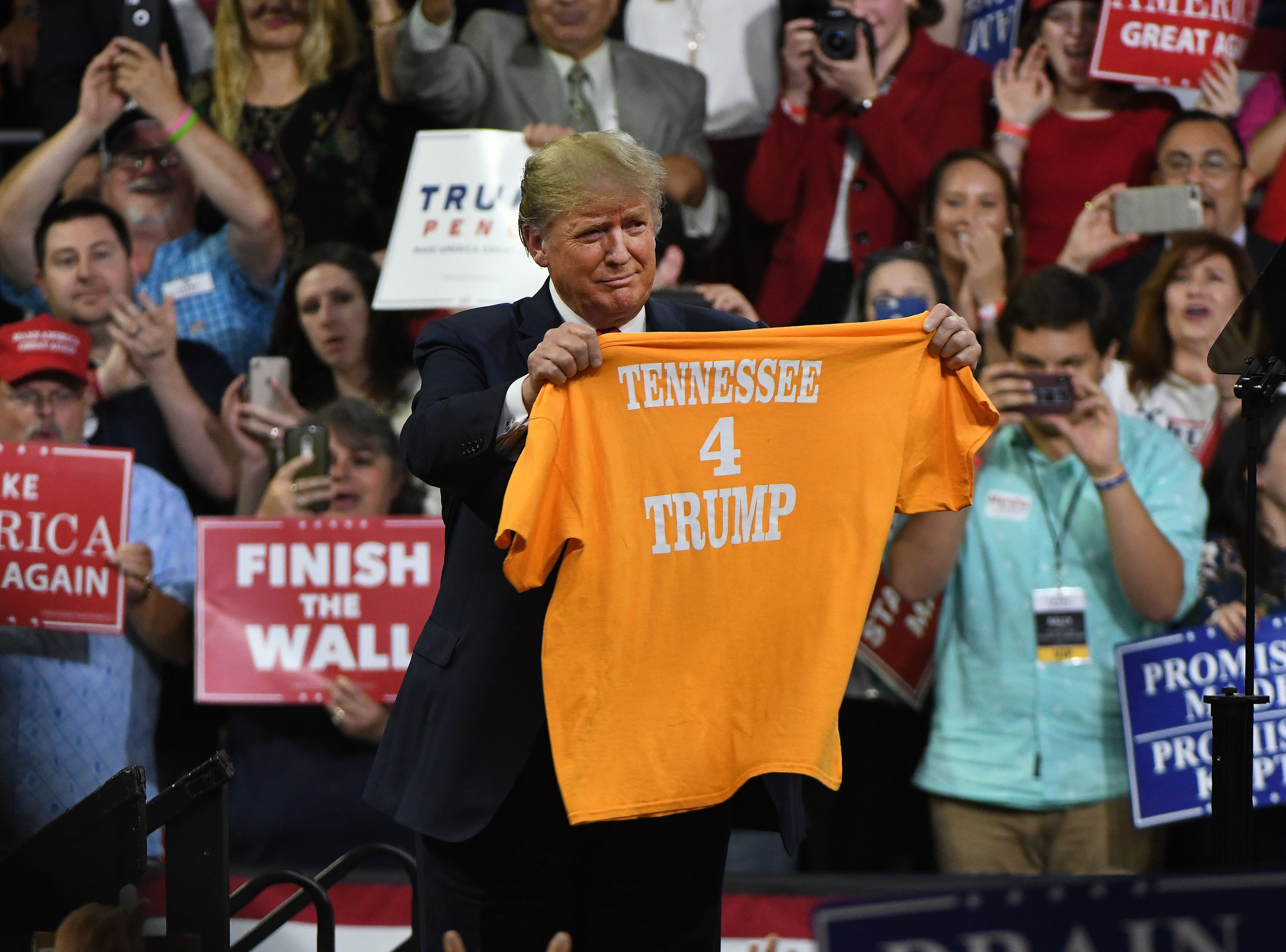 President Donald Trump holds up a Tennessee 4 Trump shirt during the Make America Great Again Rally for Marsha Blackburn at Freedom Hall on Monday, October 1, 2018 in Johnson City.