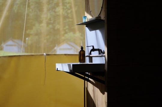 The bathroom area in a tent at Under Canvas Great Smoky Mountains includes a sink, a toilet and a shower that can be hidden behind a sliding door.