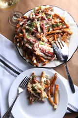 Bounty on Broad's pomme frites are topped with country ham and both goat and cheddar cheeses.