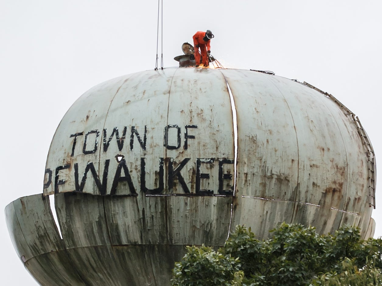 An employee of Iseler Demolition uses a torch to divide the old Town of Pewaukee water tower into hoistable sections on Monday, Oct. 1, 2018. The tower is scheduled to be completely demolished by Tuesday afternoon.