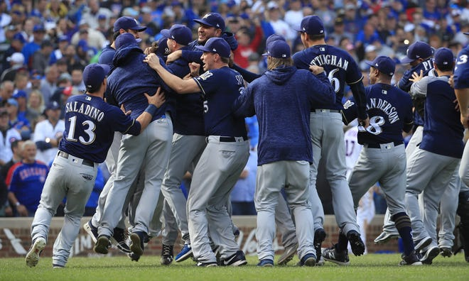 The Brewers rush the field their NL Central Division title after they beat the Cubs, 3-1, in a tiebreaker game on Monday at Wrigley Field in Chicago.