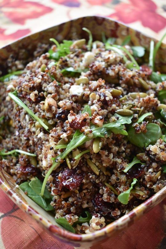 Dried cranberries, feta cheese and pumpkin seeds enhance this quinoa-arugula salad.