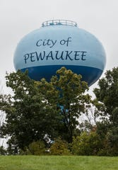 The new City of Pewaukee water tower stands not far from the old tower which is being demolished on Monday, Oct. 1, 2018.