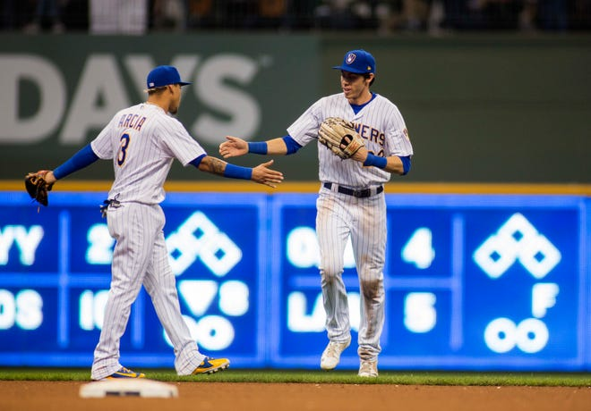 Christian Yelich (right) is congratulated by teammate Orlando Arcia as he is pulled from the game to thunderous applause in the eighth inning Sunday at Miller Park.