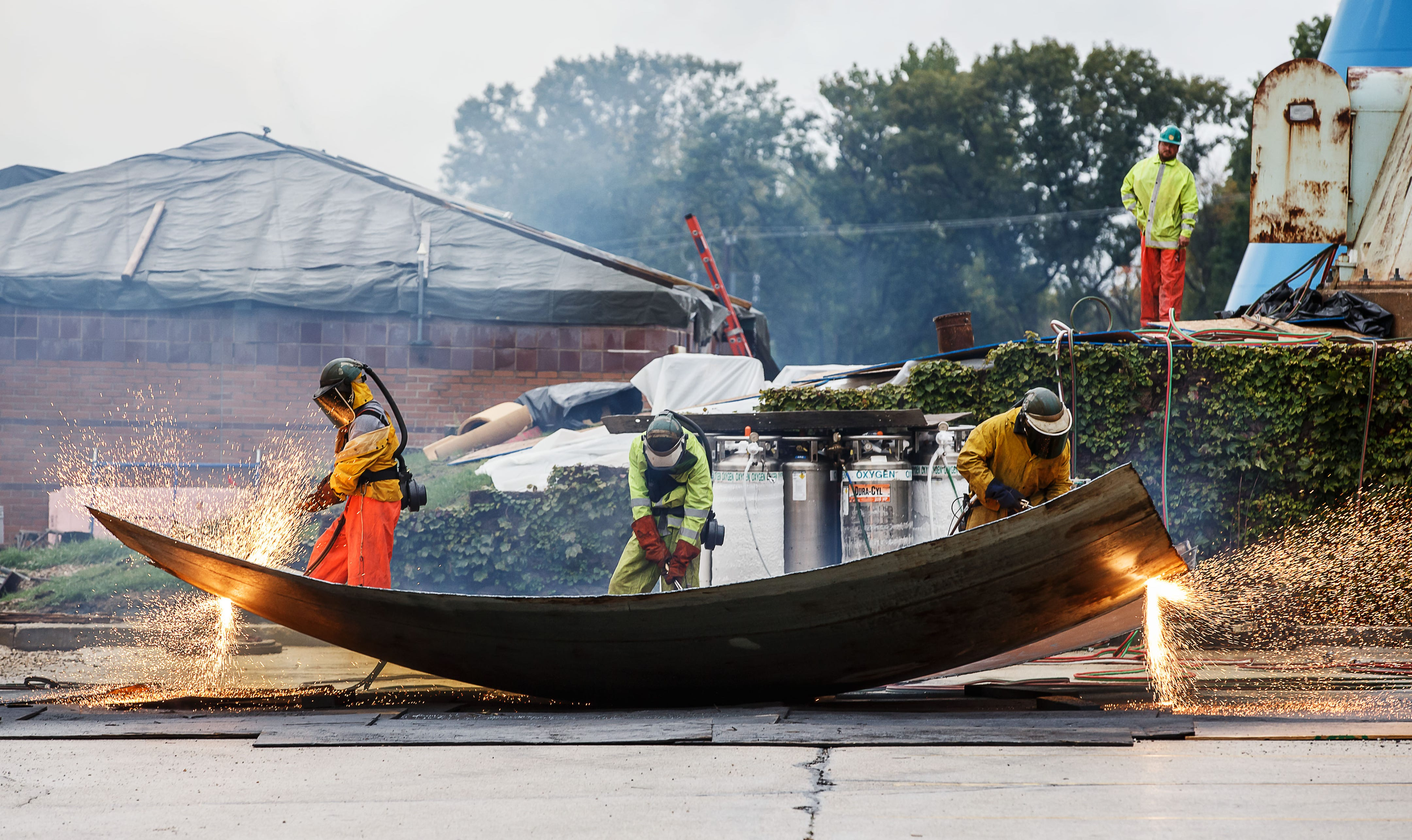 Employees of Iseler Demolition use torches to scrap out sections of the old Town of Pewaukee water tower on Monday, Oct. 1, 2018. The tower is scheduled to be completely demolished by Tuesday afternoon.