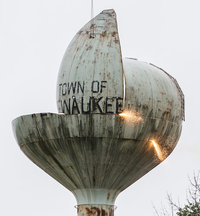 Employees of Iseler Demolition use torches to divide the old Town of Pewaukee water tower into hoistable sections on Monday, Oct. 1, 2018. The tower is scheduled to be completely demolished by Tuesday afternoon.