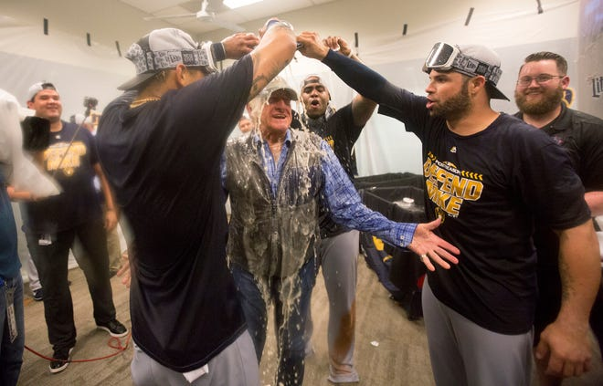 Radio voice Bob Uecker is doused with beer in the locker room after the Brewers secured a playoff berth by beating the Cardinals last Wednesday in St. Louis. Scott Paulus/Milwaukee Brewers