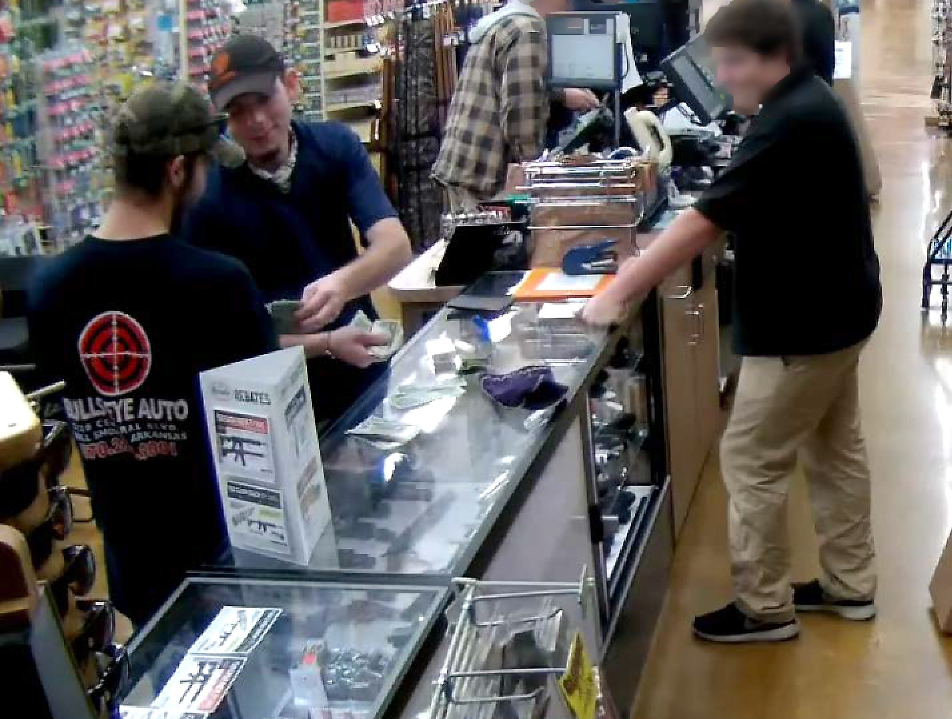 In a still frame purported to be from a surveillance video inside the Mountain Home Harps grocery store, Nicholas Ian Roos, right, hands money to Talmadge Pendergrass. Pendergrass purchased a handgun from the store and gave it Roos who less than 24 hours later murdered a Midway couple. A recently filed lawsuit filed on behalf of the couple's estate seeks monetary damages from the Company for selling the firearm.