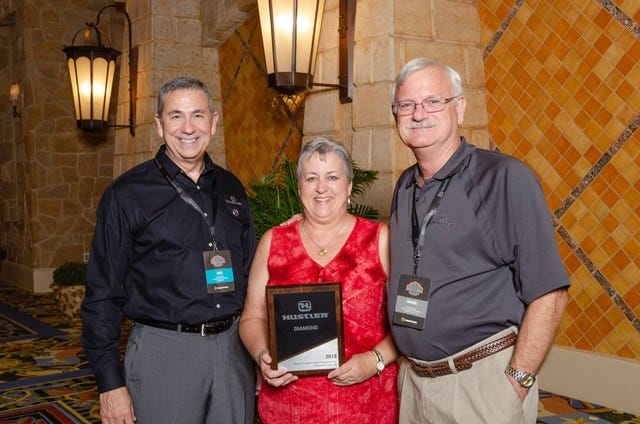 Mark and Sue Moranz of MoranzLawn and Garden received a sales award from Hustler Mowers last month in Dallas. This is the fourth consecutive year Moranz Lawn and Garden has placed in the top 15 percent of dealers nationwide. Pictured are: (from left) Hustler CEO Joe Wright, Sue Moranz and Mark Moranz.