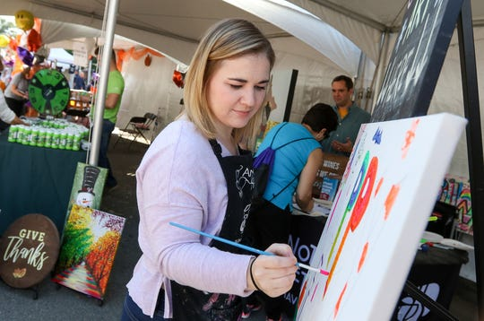 Amanda D'Angelo of Pinot's Palette paints on a community canvas during the Morristown Fall Festival on September 30, 2018.  Alexandra Pais/ The Daily Record
