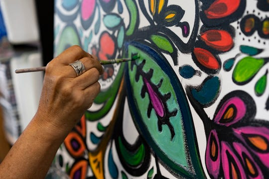 Artist and designer Jane Vallejo completes a painting she has been working on in her boutique/art studio called Art Mosaic Fashion & Art Gallery in Naples.