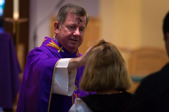 Rev. John Ludden places ashes in the form of a cross on the forehead of parishioners during an Ash Wednesday mass at St. John the Evangelist Catholic Church in North Naples on Wednesday, Feb. 18, 2015.
