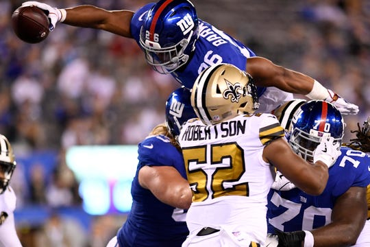 New York Giants running back Saquon Barkley (26) leaps for a touchdown in the second half. The New Orleans Saints defeat the New York Giants 33-18 on Sunday, September 30, 2018 in East Rutherford, NJ.